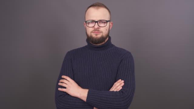porträt der jungen überraschten bärtigen kaukasischen mann mit braunen haaren, blick in die kamera und zieht den hals auf einem grauen hintergrund. - mann bart freisteller stock-videos und b-roll-filmmaterial