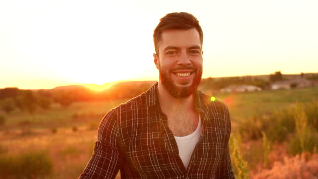 Portrait of the young bearded man on sunset. video