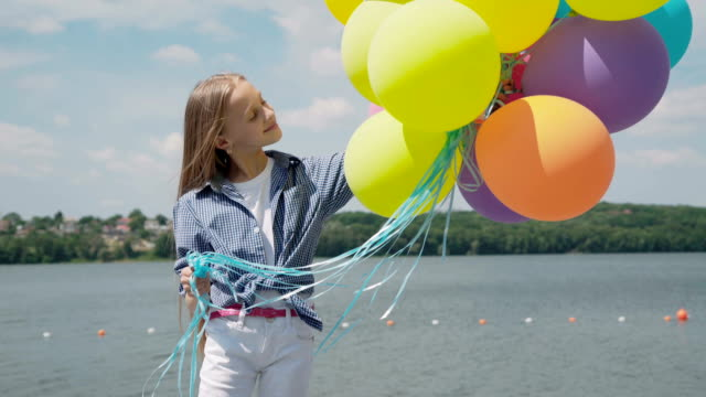 Portrait of the young playful girl with colourful balloons at a pond Portrait of the young playful girl with colourful balloons at a pond on bright day. FullHD 天の川 stock videos & royalty-free footage