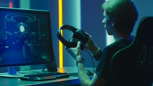porträt des jungen pro gamer spielen in first person shooter online-videospiel, gespräche mit spielern der mannschaft über mikrofon. neon farbige zimmer. e-sport cyber games internet meisterschaft. - computerspieler stock-videos und b-roll-filmmaterial