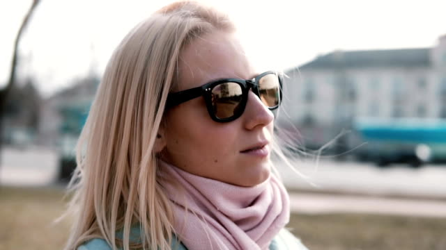Portrait of thoughful attractive Caucasian girl. Pretty adult 30s blonde female in stylish sunglasses with flying hair video