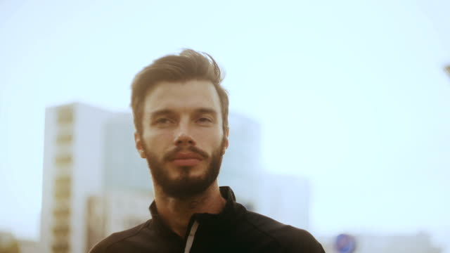 4K Portrait of thoughtful man looking forward. Bearded Caucasian handsome male in sunlight glare modern city background