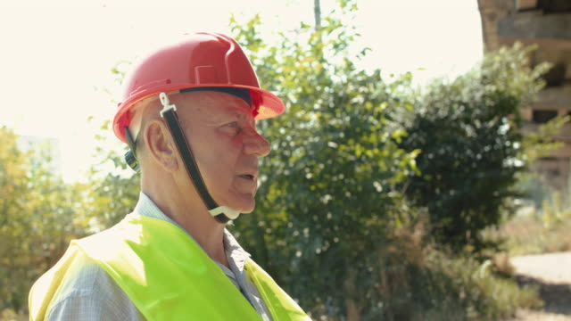 Portrait of thoughtful senior man in uniform looking around at camera in summer video