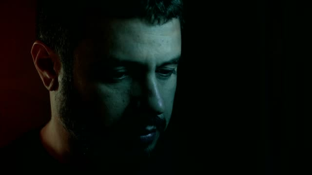 portrait of thoughtful worried handsome man thinking alone in the dark - solo un uomo video stock e b–roll