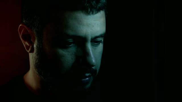 porträtt av tankeväckande orolig stilig man tänkande ensam i mörkret - endast en man bildbanksvideor och videomaterial från bakom kulisserna