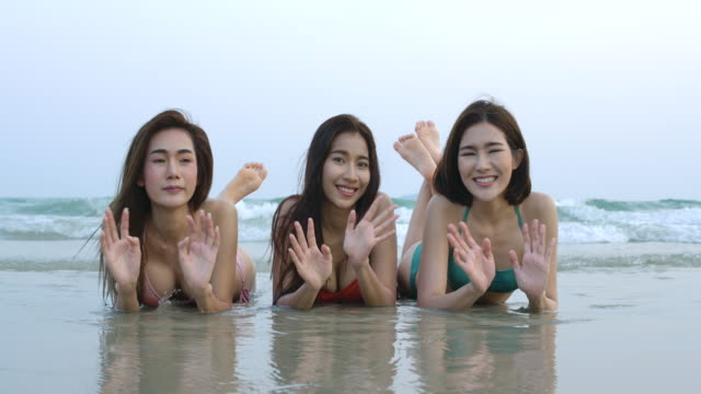 Portrait of three asian girls in bikini lying on sand together at the beach and looking at camera. Beautiful asian girl during summer vacation. celebration and relaxation concept.