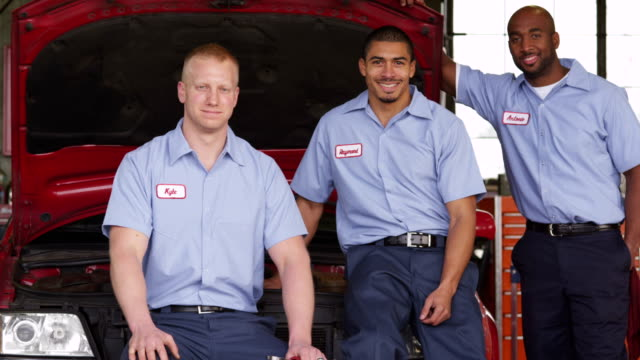 Portrait of three auto mechanics in shop video