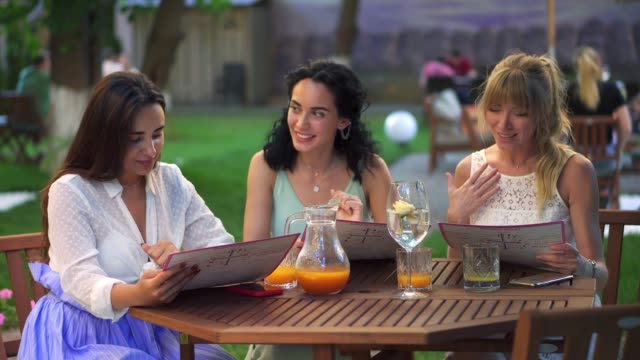 Portrait of three pretty girlfriends reading menu and having fun together in the cafe outdoors in the public park