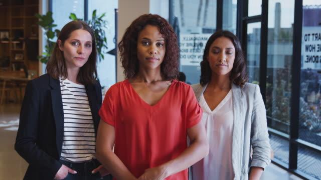 stockvideo's en b-roll-footage met portret van drie ernstige zakenvrouwen die zich in modern open bureau van plan samen bevinden - drie personen