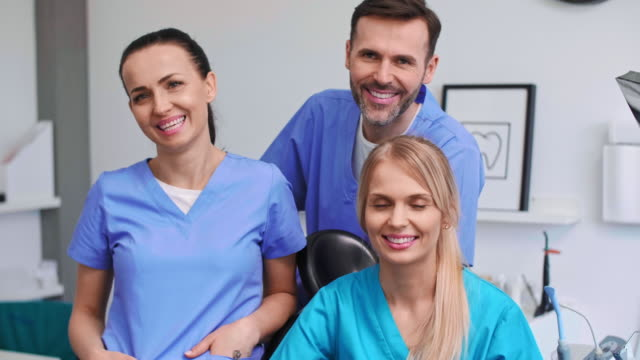 portrait of three, smiling dentists in dentist's clinic - dentist стоковые видео и кадры b-roll