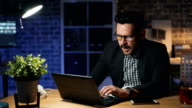 istock Portrait of tired guy working with laptop yawning sleeping on computer at night 1166012931