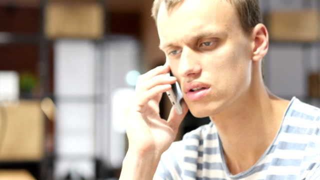 Portrait of Tired man talking on the phone, Discussing issue on phone video