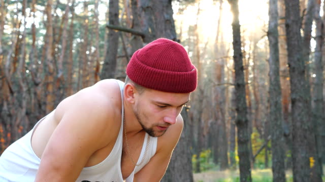 vídeos de stock e filmes b-roll de portrait of tired runner taking break after hard run training in forest. exhausted sportsman resting after outdoor workout. athletic man training at nature. concept of healthy active lifestyle. - músculo humano