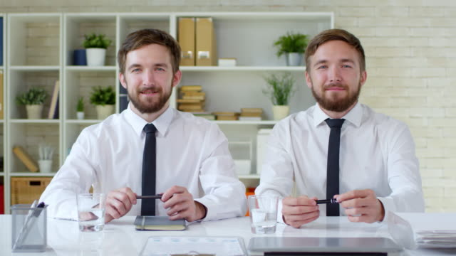portrait of twin brothers at office desk - ripetizione video stock e b–roll