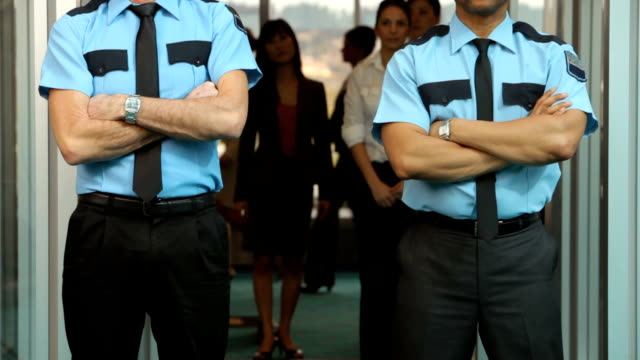 Portrait of two airport security guards HD1080p: Portrait of two airport security guards, standing in front of metal detector security staff stock videos & royalty-free footage