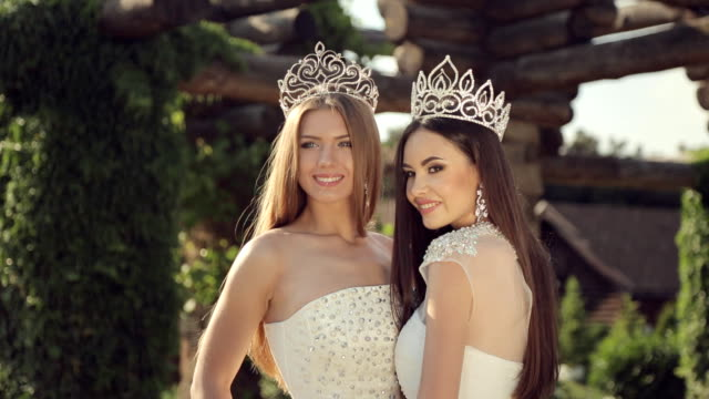 portrait of two beautiful girls in wedding dresses and tiaras outdoors in a park - prom fashion stock videos and b-roll footage