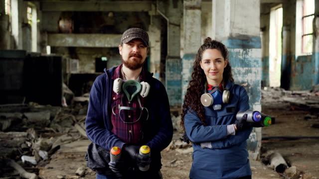 porträtt av två glada människor graffiti målare står i tomma gamla lager innehav sprayfärg och tittar på kameran. skäggig man har skyddande gas mask. - väggmålning bildbanksvideor och videomaterial från bakom kulisserna