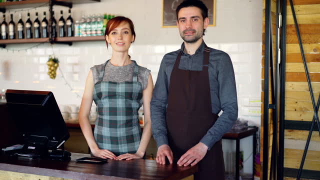 portrait of two confident waiters in aprons standing at cashier's desk in coffee-house and smiling. successful business, happy people and food service concept. - bar lokal gastronomiczny filmów i materiałów b-roll