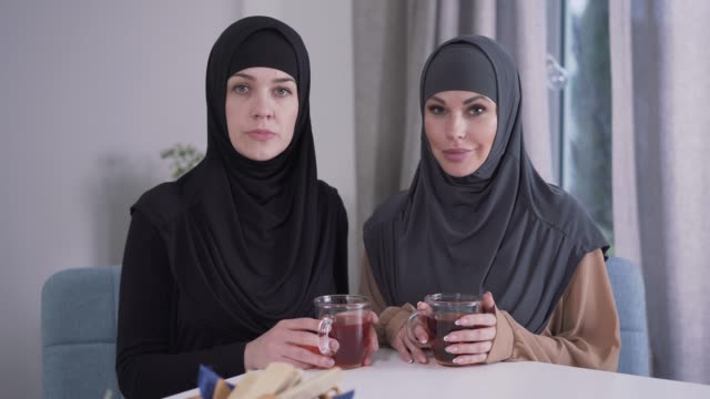 portrait of two confident women in hijabs looking at camera and smiling. modest and modern-looking ladies posing indoors. style, beauty, lifestyle. - abbigliamento religioso video stock e b–roll