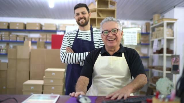 porträtt av två medarbetare tillsammans i en hantverks utrustnings affär-familjeföretag - frilansarbete bildbanksvideor och videomaterial från bakom kulisserna