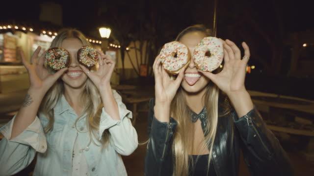vídeos de stock, filmes e b-roll de retrato de duas meninas bonitos se divertindo fazendo caretas com rosquinhas sobre olhos - junk food