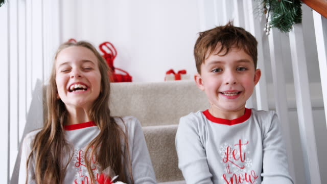 Portrait Of Two Excited Children Wearing Pajamas Sitting On Stairs Holding Stockings On Christmas Morning Excited boy and girl wearing pajamas sitting on stairs on Christmas morning - shot in slow motion christmas stocking stock videos & royalty-free footage