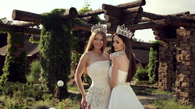 portrait of two girls in wedding dresses and crowns outdoors in a park - prom fashion stock videos and b-roll footage