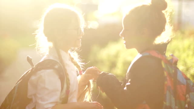 Portrait of two schoolgirls in the sun. Girls play a game, clapping hands, school bags behind their backs