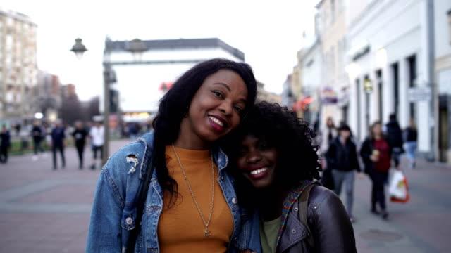 stockvideo's en b-roll-footage met portret van twee glimlachende jonge vrouw op straat-vriendschap en familieconcept - curly brown hair