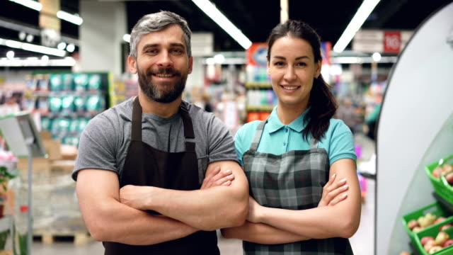 vídeos de stock e filmes b-roll de portrait of two supermarket employees attractive people in aprons standing inside shop, smiling and looking at camera. shelves with food and drinks are visible. - supermarket worker
