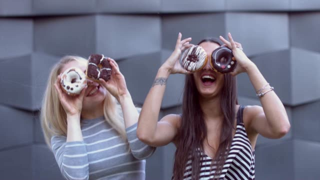 portrait of two young girls doing silly faces with donuts - bombolone video stock e b–roll