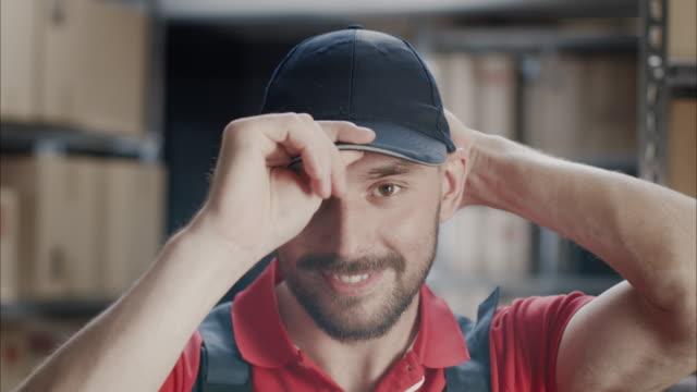 üniformalı alt kapağı bir koyarak portresi. arka plan ambar veya depo. - kep şapka stok videoları ve detay görüntü çekimi