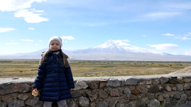 Portrait of vacation travel little girl looking at Ararat mountain landscape. Nature during summer vacations. Young kid standing at lookout looking at camera. video