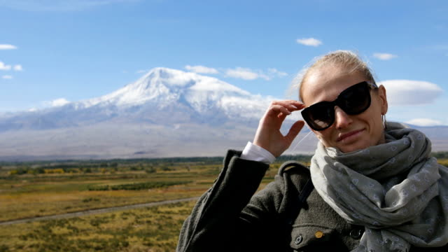 Portrait of vacation travel woman looking at Ararat mountain landscape. Nature during summer vacations. Young female standing at lookout looking at camera. video