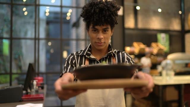 vídeos de stock, filmes e b-roll de retrato do empregado de mesa que prende a massa saboroso e fresca - brasileiro pardo