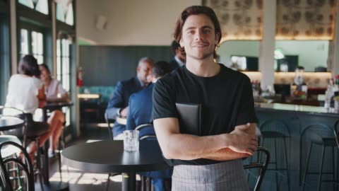 Portrait Of Waiter In Busy Cocktail Bar Of Restaurant With Customers In Background Male waiter smiling at camera with customers in background - shot in slow motion medium shot stock videos & royalty-free footage