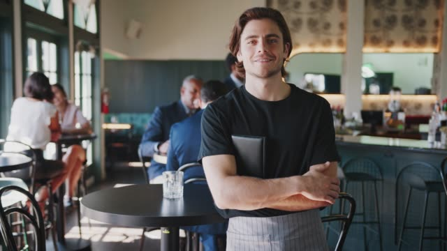 Portrait Of Waiter In Busy Cocktail Bar Of Restaurant With Customers In Background Male waiter smiling at camera with customers in background - shot in slow motion wait staff stock videos & royalty-free footage