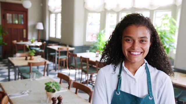 vídeos de stock e filmes b-roll de portrait of waitress standing in empty restaurant before start of service - avental