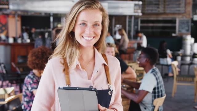 portret kelnerki w fartuchu trzymającego cyfrowy aparat fotograficzny w ruchliwej restauracji barowej uśmiecha się do kamery - nakręcony w zwolnionym tempie - kelner filmów i materiałów b-roll