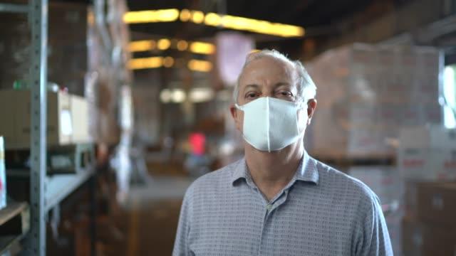 portrait of warehouse worker with face mask - prodotti supermercato video stock e b–roll