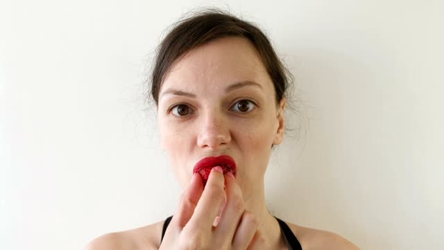 Portrait of woman eating strawberries. Front view.