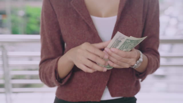 Portrait of Woman holding Bunch US dollar money and looking at camera