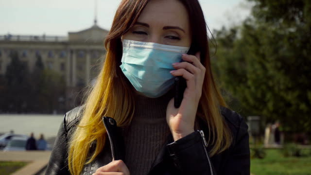Porträtt av kvinna i skyddande ansiktsmask ringer och talar med mobiltelefon under pandemi eller epidemi i staden video