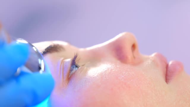 Portrait of woman on phonophoresis face procedure with hyaluronic acid gel. video