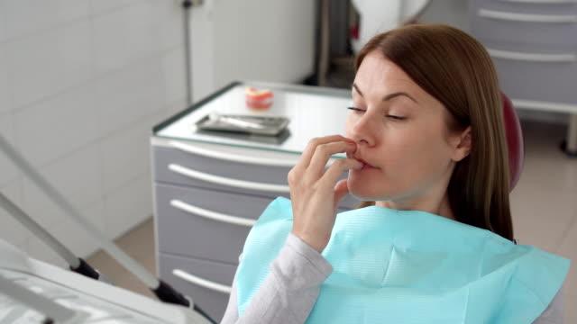 Retrato de paciente mujer en clínica dental. Esperando en el sillón dental para el estomatólogo. Chequeo dental - vídeo