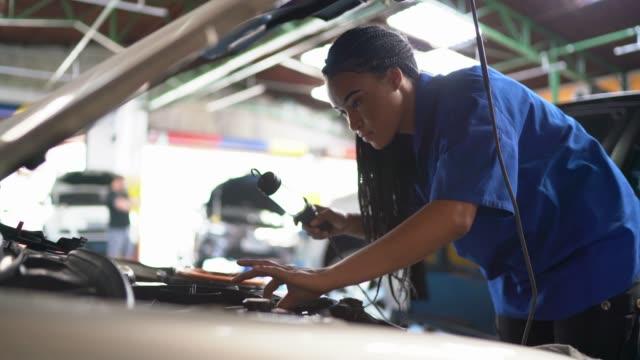 Video Portrait of woman repairing a car in auto repair shop