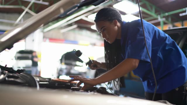 Portrait of woman repairing a car in auto repair shop video