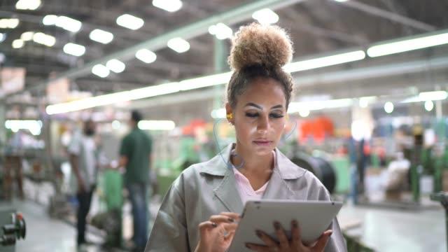 vídeos de stock, filmes e b-roll de retrato da mulher que usa a tabuleta digital na indústria - automatizado