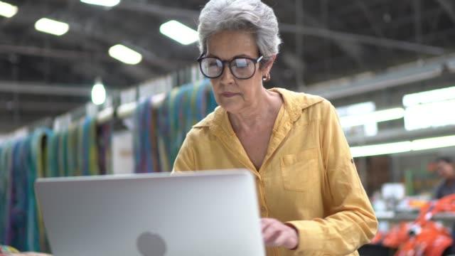 porträt der frau mit laptop in der industrie - kurzwaren stock-videos und b-roll-filmmaterial