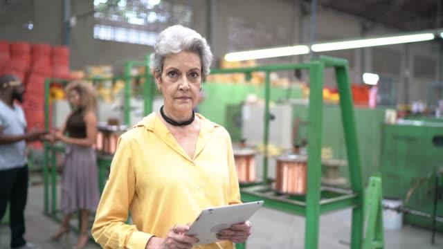 vídeos de stock e filmes b-roll de portrait of woman using mobile in industry - senior business woman tablet